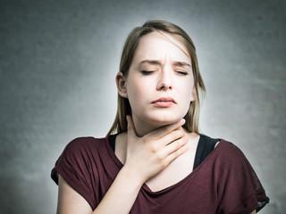 Junge Frau hat Halsschmerzen