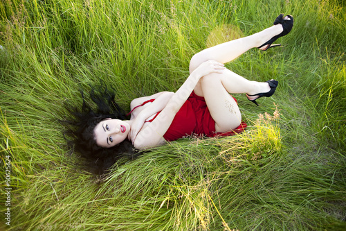 Sexy woman lying on the green grass. Red dress and high heels