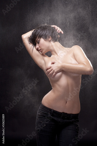 Wet sexy topless woman. Fine spray of water.