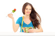 Young woman eating a salad isolated on white background