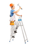Full length portrait of a repairman on a ladder working with a h