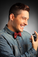 Portrait of a smiling handsome male applying perfume