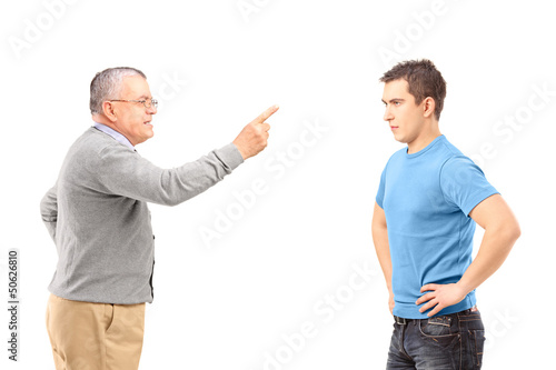 Angry father reprimanding his son with finger