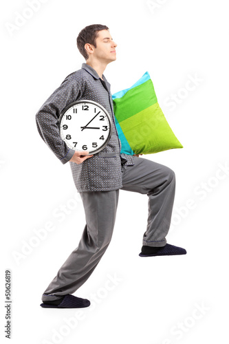 Full length portrait of a sleepwalker with a pillow and a clock