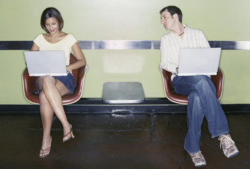 Young man peering at young woman's laptop