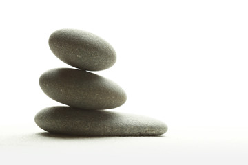 Three smooth stones on sand