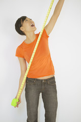 Young woman stretching a measuring tape