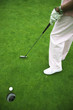 Male golfer putting ball into hole