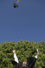 Elated male graduate throws cap into air