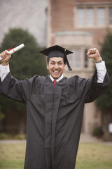 Portrait male graduate in cap with diploma and arms raised
