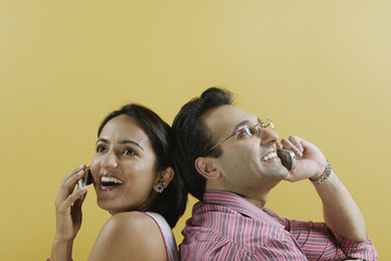 Couple back to back talking on mobile phones