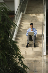 Business with laptop sitting on steps