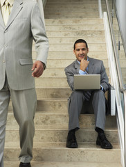Businessman sitting on steps with laptop