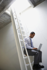 Businessman sitting on ladder with laptop