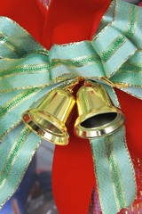 Green bow and golden bell attached to the gift.