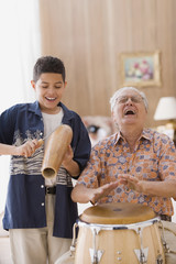 Older man and grandson playing percussion instruments