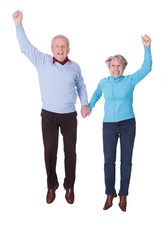 Portrait Of Senior Couple Jumping In Joy