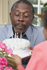 Senior African American man blowing out birthday candles