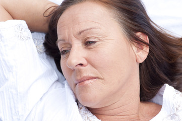 Sad contemplating mature woman resting in bed