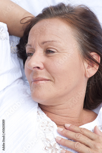 Relaxed mature woman resting in bed