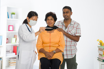 indian senior citizen health check with a chinese female doctor