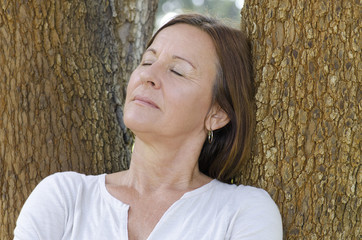 Mature woman relaxed closed eyes outdoor