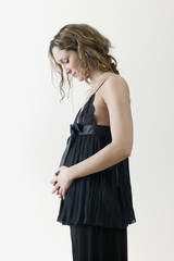 Pregnant woman in fancy clothing looking at stomach