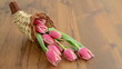 Rack focus of cornucopia basket with pink tulips