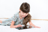 Little girl playing with a tablet