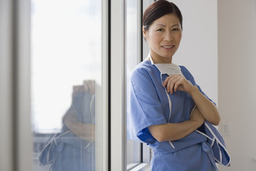 Asian female doctor leaning against window smiling