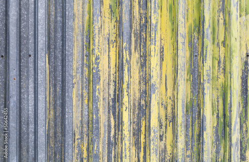 Ridged yellow painted old metal wall background texture
