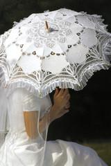 Braut mit weisem Schirm aus Spitze
