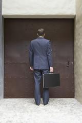 Hispanic businessman standing at doorway