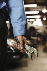 Male auto mechanic holding vice grips