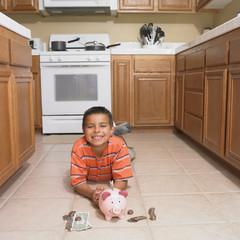 Hispanic boy with piggybank on floor