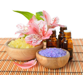 Essential oil, sea salt and flowers on a white background