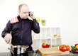 Man taking a call on his mobile while cooking
