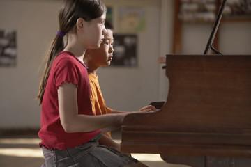 Multi-ethnic boy and girl playing piano