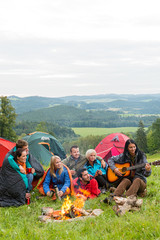 Camping friends playing guitar beside fire nature