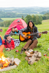 Camping friends lying tents girl playing guitar