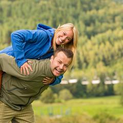 Couple having piggyback ride outside green nature