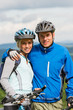 Young sporty couple with mountain bikes in helmet