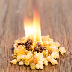 Brennender Weihrauch mit Flamme auf Holz