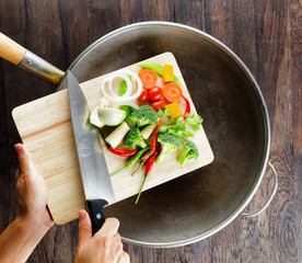 Fresh vegetables on the cutting board are falling in the wok. Co