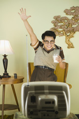 Nerdy Asian man cheering in front of television