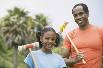 African father and daughter holding croquet mallets