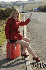 Woman sitting on a suitcase thumbing a lift