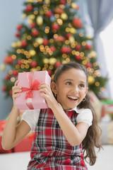 Hispanic girl shaking Christmas gift