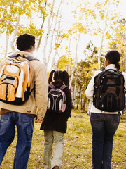 African family wearing back packs in woods
