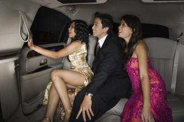 Multi-ethnic friends sitting in limousine